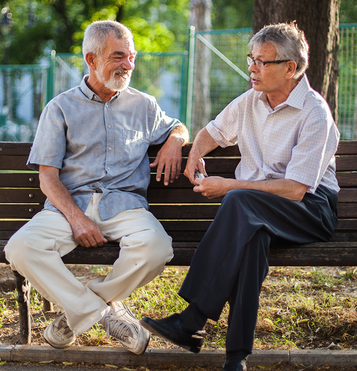 2 senior men sitting on a park bench talking