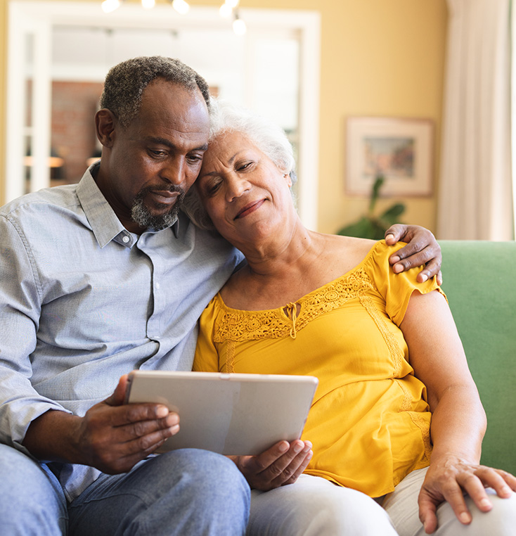 2 seniors with arms around each other while looking at computer tablet