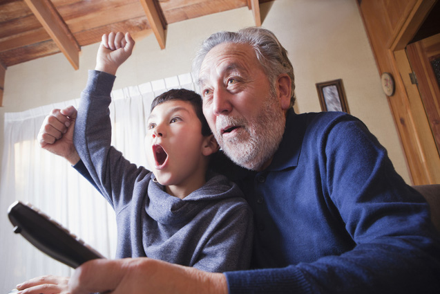 Grandfather and grandson cheering for sports game on television