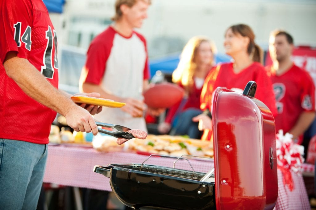 Extensive series of a multi-ethnic group of fans tailgating outside a stadium before a football game. Includes tickets, cooking, eating and fun.